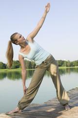 Junge Frau macht Yoga auf einem Steg