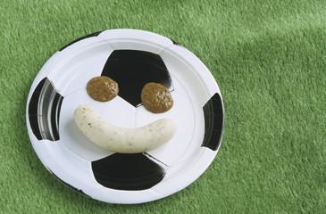 Deutsche Weisswurst und süßer Senf formen Gesicht auf Teller, Thema Fußball