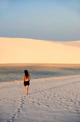 Hübsche junge Frau läuft durch den Sand auf Lagune zu
