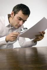 Ein Mann liest ein Dokument mit Lupe