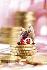 Mann im Rollstuhl auf Stapel von Münzen, Symbolszene mit Figuren