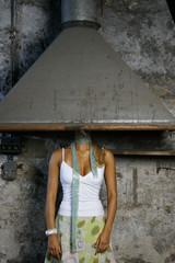 Junge Frau steht versteckt unter Schornstein