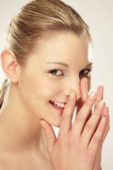 Junge Frau lächelnd, berührt die Nase