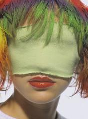 Junge Frau mit einer Maske und coloriertem Haar