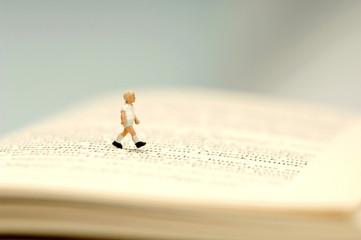 Figur eines Jungen zu Fuß über offenes Buch