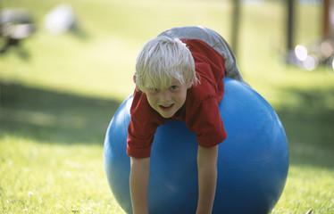 Junge liegend auf großen blauen Gummiball