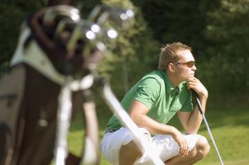 Golfspieler hockend, plant seinen nächsten Schlag
