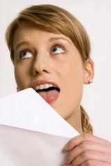 Junge Frau leckt Umschlag ab