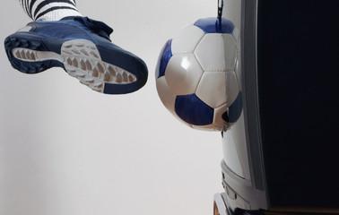 Mann schießt Fußball in Fernseher
