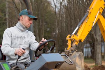 Construction worker driving road roller on backhoe background