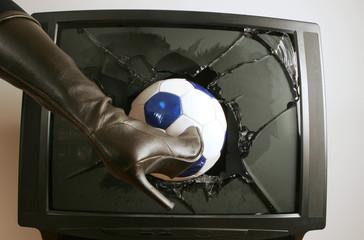 Frau schießt Fußball in Fernseher