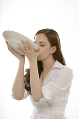 Junge Frau trinkt Suppe direkt aus dem Teller
