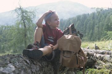 Junge sitzt auf Baumstamm