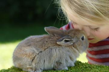 Mädchen im Streichelzoo mit Kaninchen