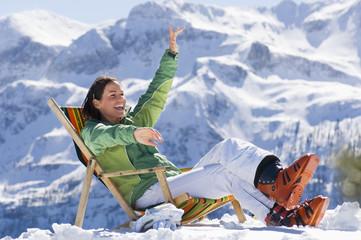 Frau in den Bergen sitzt im Liegestuhl
