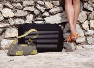 Frau sitzen an der Wand mit Koffer und Handtasche,