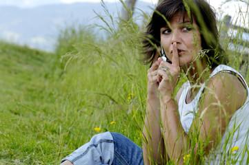 Frau sitzen im Feld mit Handy, Finger auf die Lippen