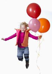 Mädchen hält Luftballons und springt