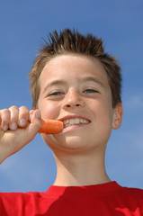 Junge isst gesund, eine Karotte