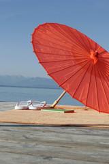 Deutschland, Bayern, Starnberger See, Sonnenschirm und Badeschuhe auf Anlegestelle