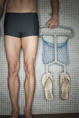 Mann steht in Umkleidekabine, hält Kleiderbügel mit Flip-Flops