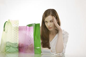 Junge Frau mit Einkaufstüten, rechnet Ausgaben mit Taschenrechner
