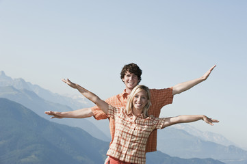 Junges Paar, Arme ausgestreckt, lächelnd