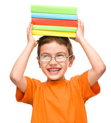 Little boy is holding a pile of books