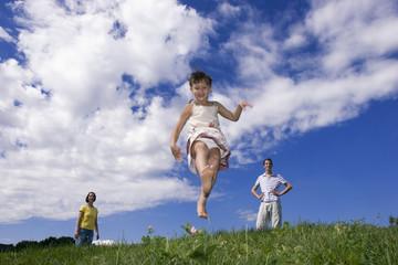 Mädchen springt auf einer Wiese herum