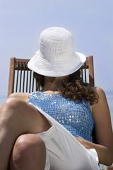 Junge Frau sitzt auf Liegestuhl am Steg