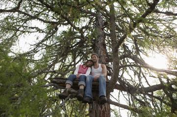 Junges Paar sitzt im Baumhaus, umarmt sich