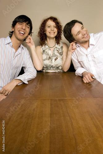 Junge Frau zieht ihren zwei Männern am Ohr