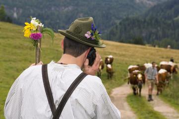 Mann telefoniert in den Bergen, Rückansicht