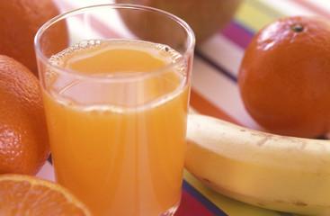 Glas frischer Orangensaft mit Früchten im Hintergrund