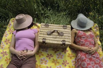 Frauen entspannen auf der Wiese, mit Hut über dem Gesicht
