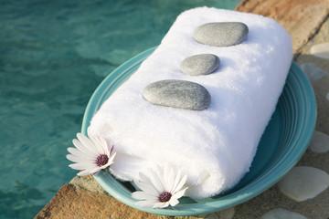 Handtuch, Steine __und Blüten auf Kunststoffteller