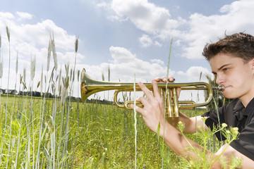 Junger Mann spielt Trompete im Feld, Seitenansicht