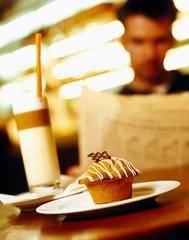 Muffin auf Teller, Person im Hintergrund liest Zeitung