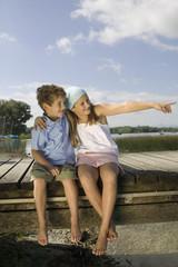 Junge und Mädchen sitzen auf Steg