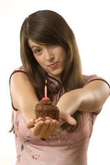 Junge Frau bläst Kerzen aus, auf Torte