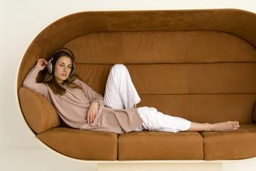 Frau jung sitzen auf dem Sofa, das Tragen von Kopfhörern