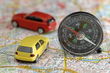 Spielzeugautos und Kompass auf Stadtplan