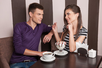young couple eating ice-cream in cafe.