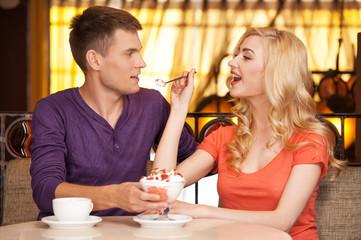 beautiful girl giving ice-cream to man.