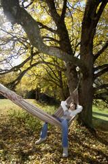 Frau liegt in der Hängematte, Herbst