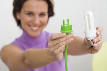 Frau mit grünem Stecker und Leuchtmittel