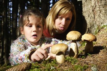 Mutter und Tochter sammeln Steinpilze im Wald