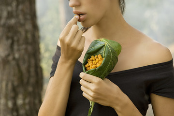 Beautiful woman  eating wild raspberry in the forest