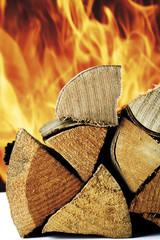 Brennholz gestapelt, Feuer im Hintergrund