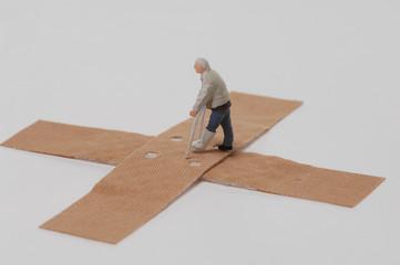 Kunststoff-Figur auf Krücken läuft über Pflaster
